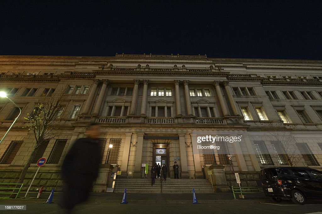A pedestrian walks past the Bank of Japan headquarters at night in Tokyo, Japan, on Monday, Dec. 10, 2012. Japan's bond market is signaling concern that a government run by Shinzo Abe will ramp up spending to revive growth, adding to a debt burden already twice the size of the nation's economy. Photographer: Akio Kon/Bloomberg via Getty Images