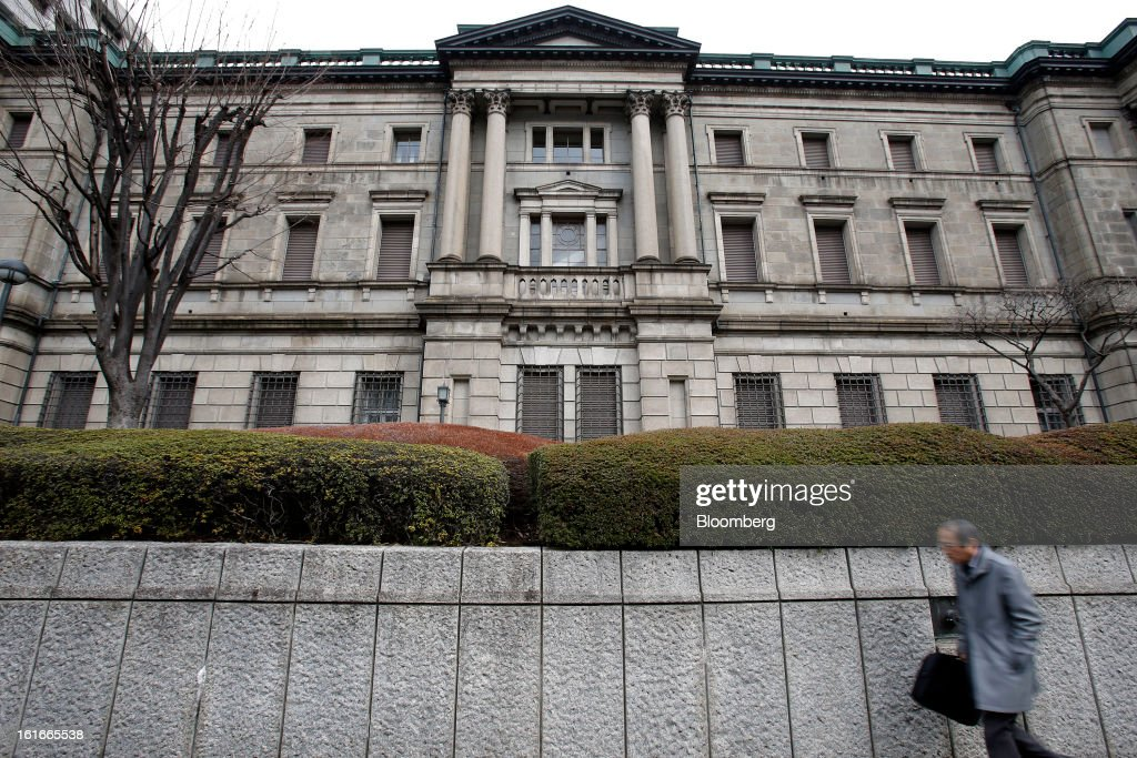 A pedestrian walks past the Bank of Japan headquarters in Tokyo, Japan, on Thursday, Feb. 14, 2013. Asian stocks rose after the Bank of Japan maintained its asset-purchasing program before its governor steps down next month. Photographer: Kiyoshi Ota/Bloomberg via Getty Images