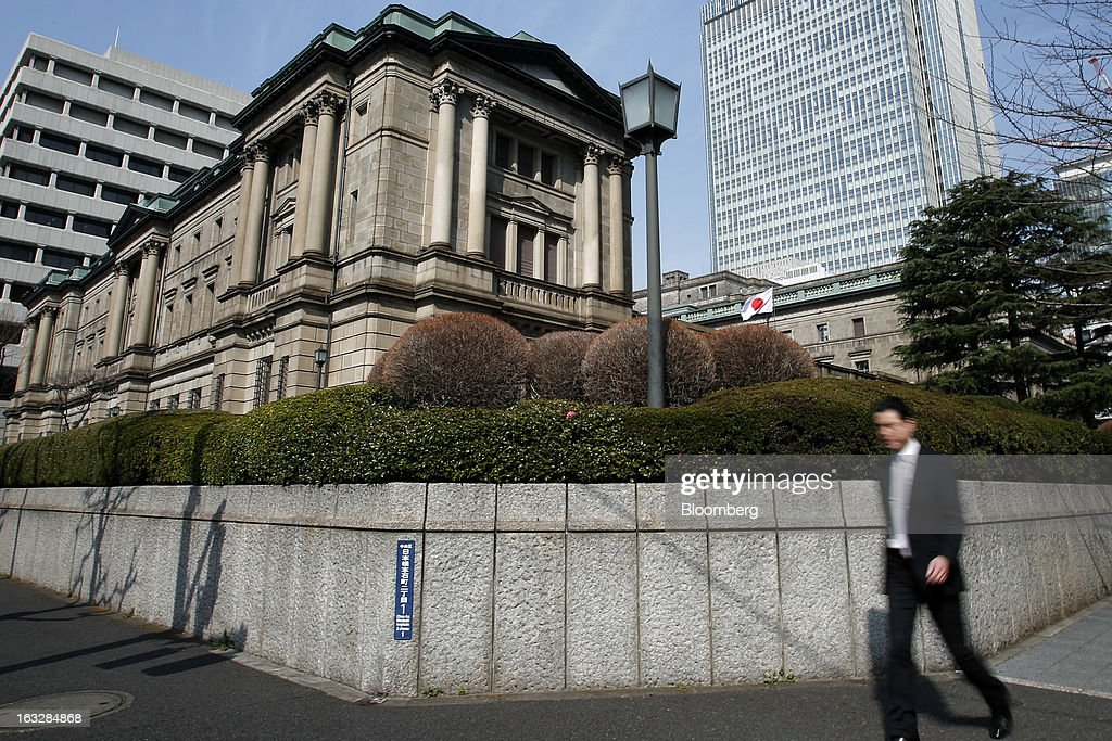 A pedestrian walks past the Bank of Japan headquarters in Tokyo, Japan, on Thursday, March 7, 2013. The Bank of Japan rejected a call for an immediate start to open-ended asset purchases in Governor Masaaki Shirakawa's final meeting before a new leadership takes over at the central bank. Photographer: Kiyoshi Ota/Bloomberg via Getty Images