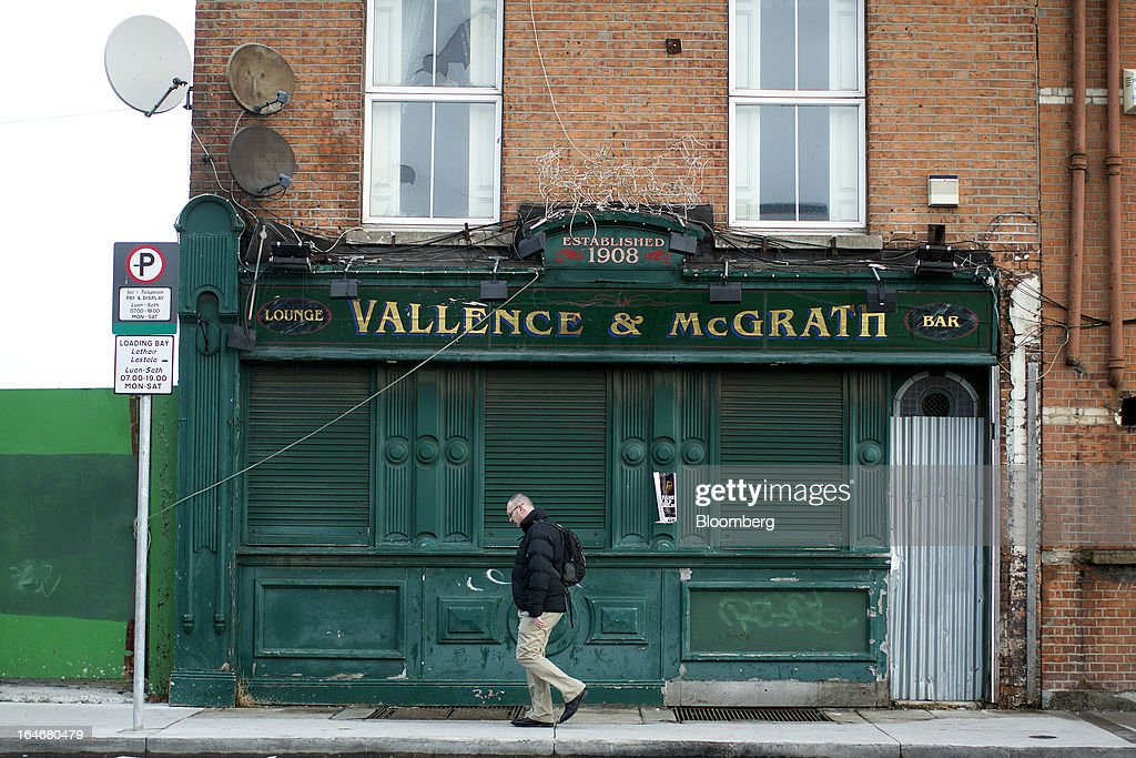 A pedestrian walks past the closed down Vallence & McGrath bar on North Wall Quay in Dublin, Ireland, on Friday, March 15, 2013. Ireland's renewed competiveness makes it a beacon for the U.S. companies such as EBay, Google Inc. and Facebook Inc., which have expanded their operations in the country over the past two years. Photographer: Simon Dawson/Bloomberg via Getty Images