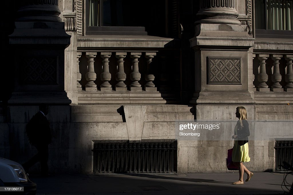 A pedestrian walks past the columns of an old building in London, U.K., on Monday, July 8, 2013. Britain's economy could be in line for a period of 'strong catch-up growth' once it gets through the current weakness, according to Capital Economics Ltd. Photographer: Simon Dawson/Bloomberg via Getty Images