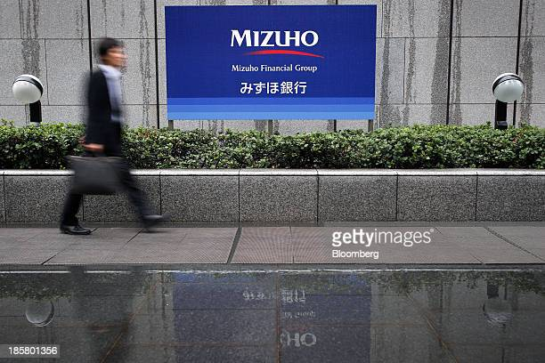 A pedestrian walks past the corporate logo of Mizuho Financial Group Inc displayed outside the Mizuho Bank Ltd headquarters in Tokyo Japan on Friday...