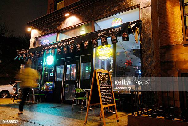 A pedestrian walks past the Downtown Bar and Grill in the Brooklyn borough of New York US on Wednesday Dec 13 2007 After dive bars trendy bars sports...