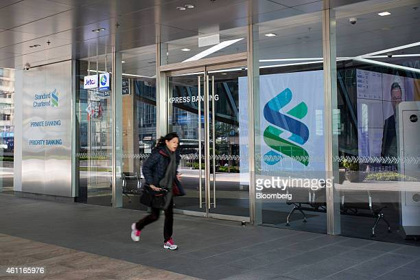 A pedestrian walks past the entrance of a Standard Chartered Plc bank branch in the Central business district of Hong Kong China on Thursday Jan 8...