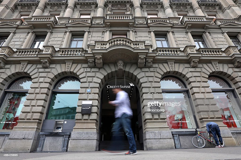 A pedestrian walks past the entrance to Credit Suisse Group AG's headquarters in Zurich, Switzerland, on Tuesday, May 6, 2014. Credit Suisse is close to resolving a U.S. tax-evasion probe with an agreement that might include a penalty of more than $1 billion, after creating a separate entity last year to house the businesses involved. Photographer: Philipp Schmidli/Bloomberg via Getty Images