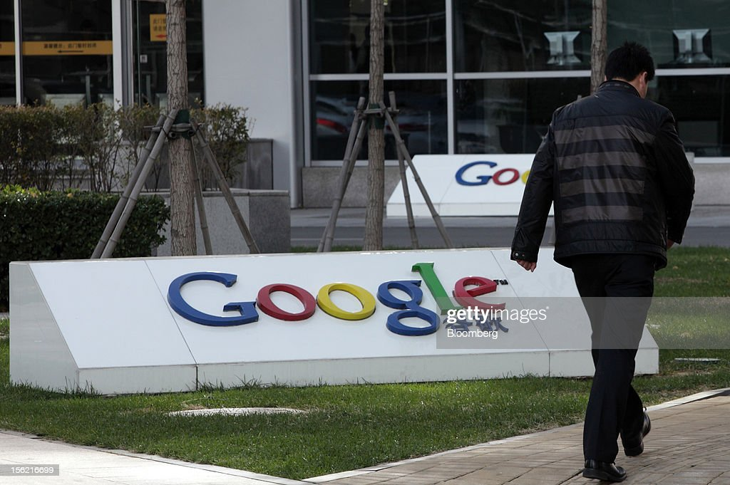 A pedestrian walks past the Google Inc. logo displayed outside the building housing the company's China headquarters in Beijing, China, on Monday, Nov. 12, 2012. Google Inc. reported higher traffic patterns on its sites in China after the company earlier said there was an unusual decline in the country, and an Internet monitor said company services were blocked there. Photographer: Tomohiro Ohsumi/Bloomberg via Getty Images