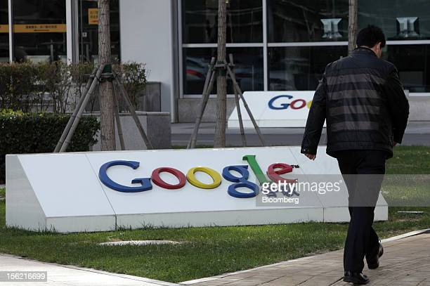 A pedestrian walks past the Google Inc logo displayed outside the building housing the company's China headquarters in Beijing China on Monday Nov 12...