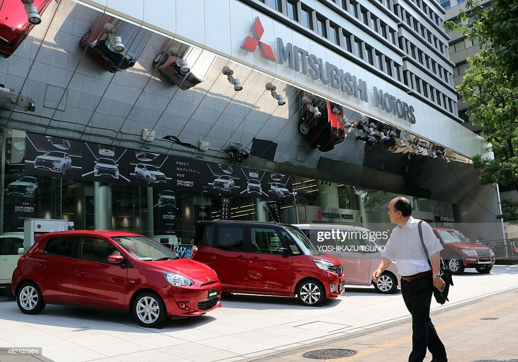 A pedestrian walks past the headquarters of Japanese automaker Mitsubishi Motors in Tokyo on July 27 2015 Mitsubishi will end vehicle production in...