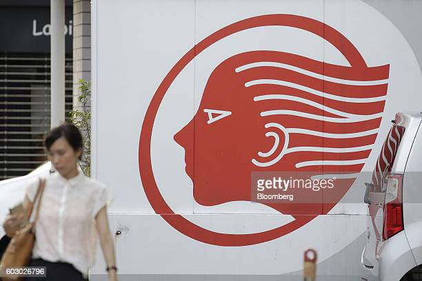 A pedestrian walks past the Idemitsu Kosan Co logo displayed at one of the company's gasoline stations in Tokyo Japan on Friday Aug 12 2016 At an...