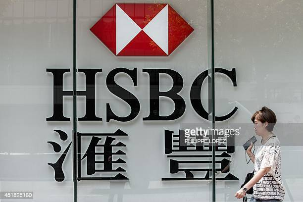 A pedestrian walks past the logo of HSBC outside a branch of the bank in Hong Kong on July 8 2014 Global bank HSBC has downgraded its investment...