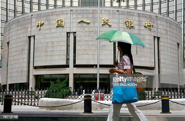 A pedestrian walks past the People's Bank of China also known as China's Central Bank in Beijing 22 August 2007 China's bid to tighten liquidity...