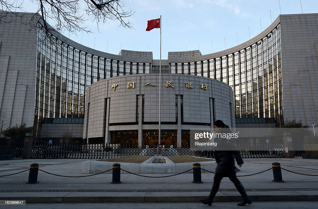 A pedestrian walks past the People's Bank of China (PBOC) headquarters in Beijing, China, on Friday, March 1, 2013. China's economy expanded 7.9 percent in the final three months of 2012 from a year earlier, the first pickup in two years. The pace may accelerate to 8.2 percent in the three months through March, according to the median estimate of 23 analysts surveyed by Bloomberg News in February. Photographer: Tomohiro Ohsumi/Bloomberg via Getty Images