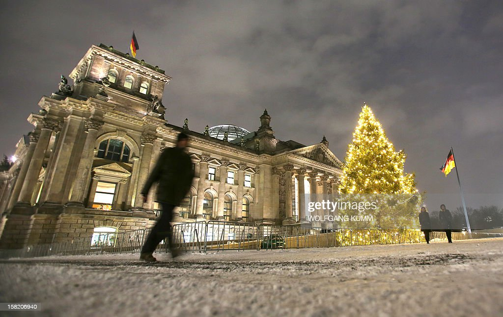 A pedestrian walks past the Reichstag, the building housing the lower house of parliament with its Christmas tree lit up on December 11, 2012. AFP PHOTO / WOLFGANG KUMM GERMANY OUT