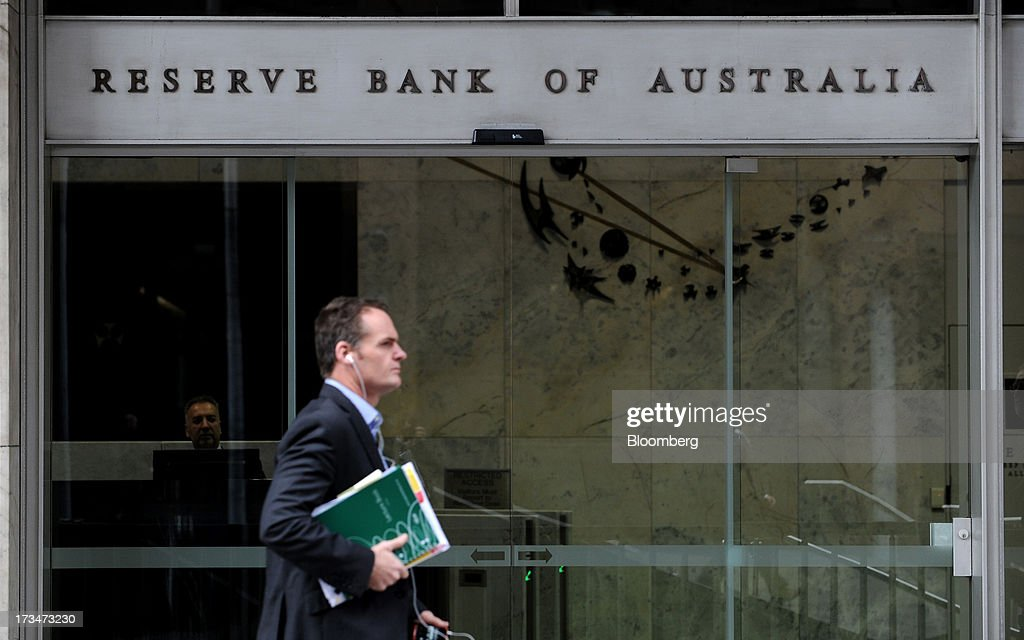 A pedestrian walks past the Reserve Bank of Australia (RBA) headquarters in the central business district of Sydney, Australia, on Monday, July 15, 2013. While the RBA previously needed higher interest rates to control price pressures as the Australian economy expanded since 1991 without a recession, Governor Glenn Stevens has slashed the cash target, predicting a mining boom will wane. Photographer: Dan Himbrechts/Bloomberg via Getty Images