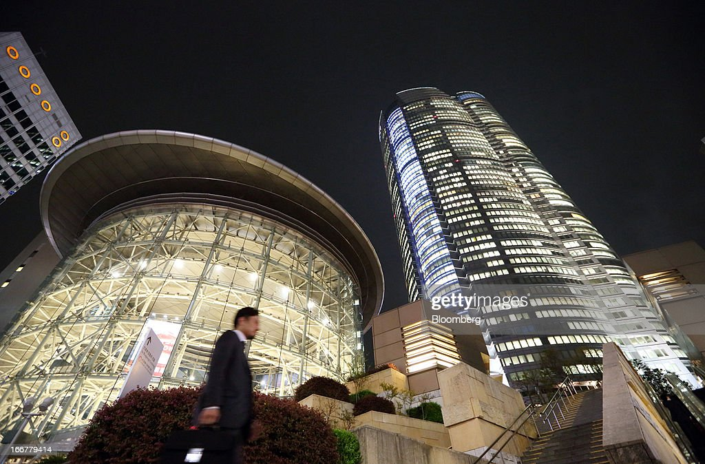 A pedestrian walks past the Roppongi Hills Mori Tower, operated by Mori Building Co., at night in Tokyo, Japan, on Tuesday, April 17, 2013. While financial firms have cut staff in Japan, technology companies have boosted hiring, and as bankers vacated offices at Roppongi Hills, companies including Google Inc. and Lenovo Group Ltd. moved in. As early as this month, Apple Inc. will also make the complex its home in Japan, two people familiar with the plan said in January. Photographer: Tomohiro Ohsumi/Bloomberg via Getty Images