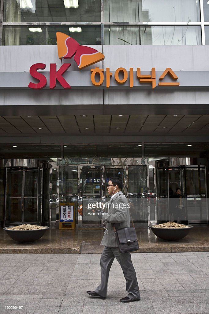A pedestrian walks past the SK Hynix Inc. headquarters in Seoul, South Korea, on Monday, Jan. 28, 2013. Hynix is scheduled to release full-year earnings on Jan. 30. Photographer: Jean Chung/Bloomberg via Getty Images