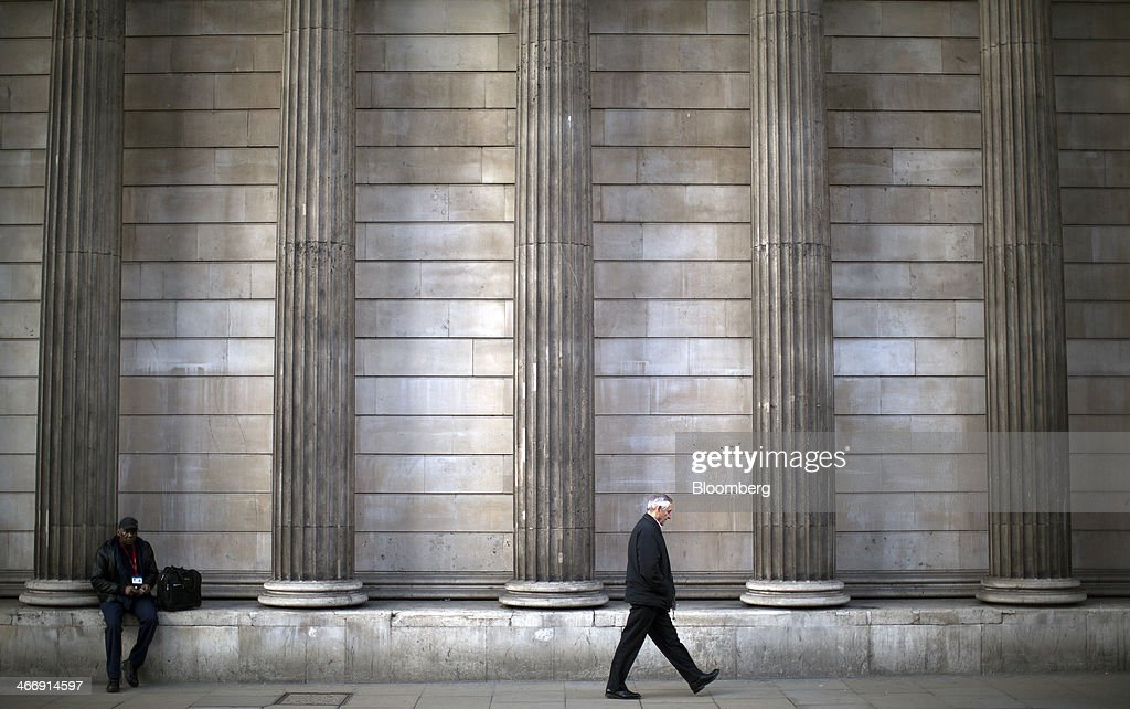 A pedestrian walks past the stone columns of the Bank of England in London, U.K., on Tuesday, Feb. 4, 2014. Between 2007 and 2011, policy makers in London lagged behind their American counterparts in cutting rates and adopting emergency policy measures in response to the financial crisis. Photographer: Simon Dawson/Bloomberg via Getty Images