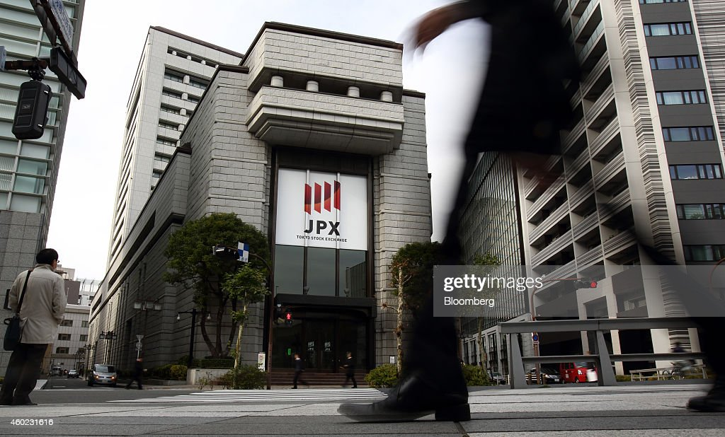 A pedestrian walks past the Tokyo Stock Exchange operated by Japan Exchange Group Inc in Tokyo Japan on Wednesday Dec 10 2014 Japanese stocks fell by...