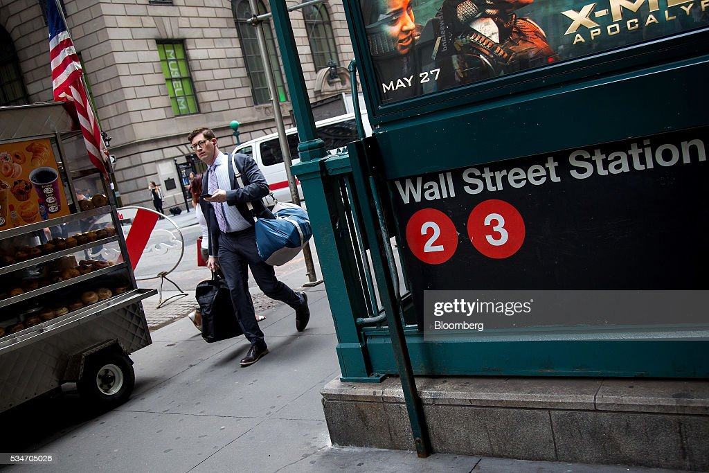A pedestrian walks past the Wall Street subway station near New York Stock Exchange (NYSE) in New York, U.S., on Friday, May 27, 2016. U.S. stocks edged higher, with the S&P 500 on course for its biggest weekly advance since March, while investors awaited remarks from Federal Reserve Chair Janet Yellen for hints on the timing of the next interest-rate increase. Photographer: Michael Nagle/Bloomberg via Getty Images