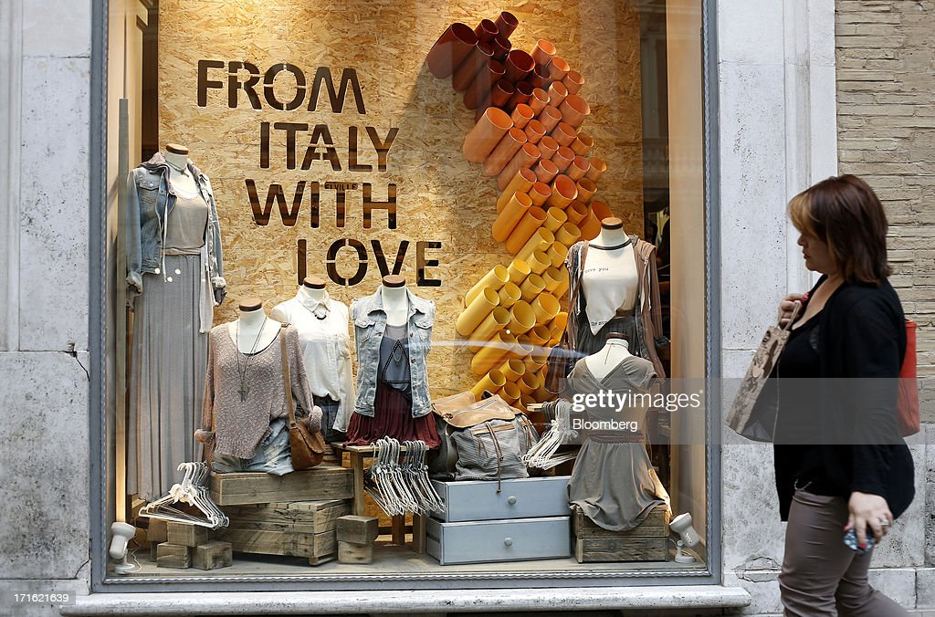 A pedestrian walks past the window display of a clothes store which reads 'From Italy With Love' in Rome, Italy, on Wednesday, June 26, 2013. Italian household confidence rose this month as consumers grew optimistic about the country's outlook as Prime Minister Enrico Letta's government plans to cut taxes and boost youth employment. Photographer: Alessia Pierdomenico/Bloomberg via Getty Images