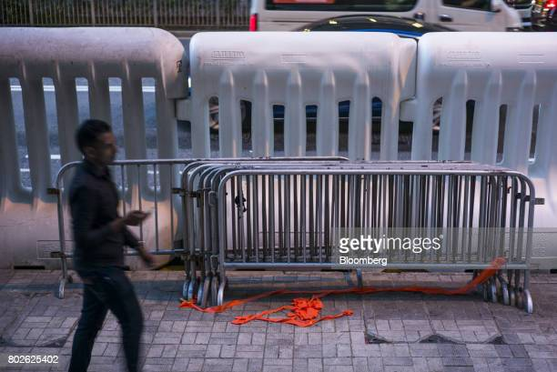 A pedestrian walks past water barricades near the Hong Kong Convention and Exhibition Center ahead of Chinese President Xi Jinping's arrival in Hong...