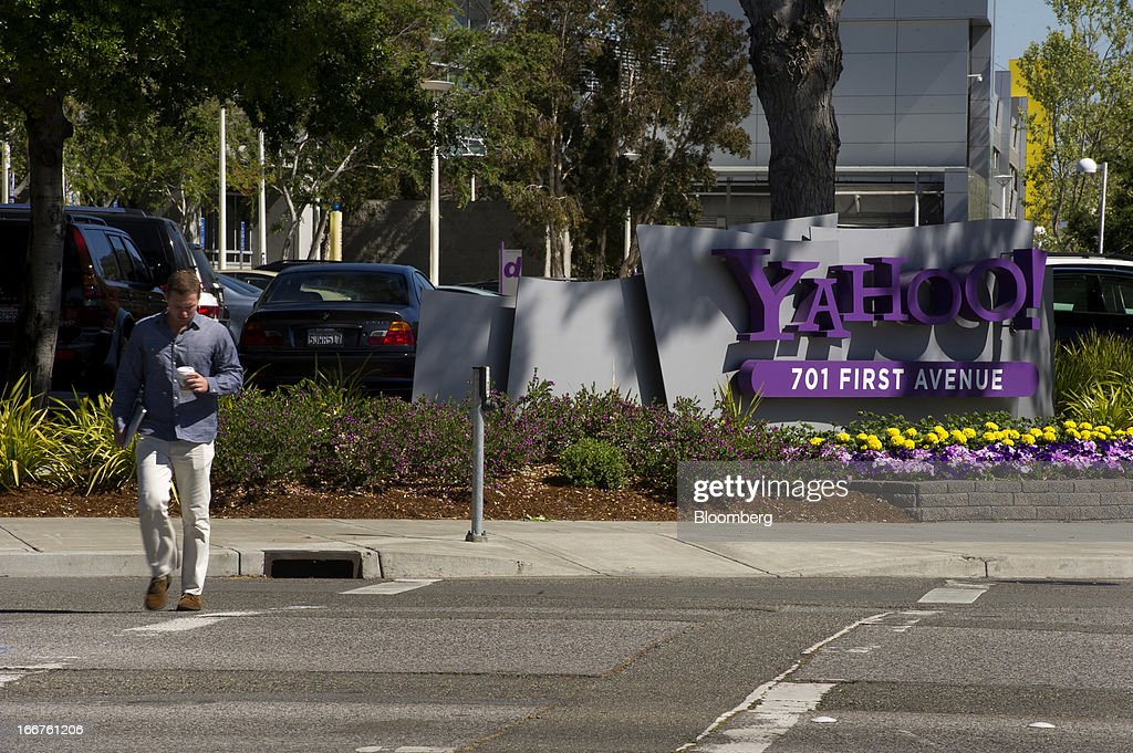 A pedestrian walks past Yahoo! Inc. signage displayed at the company's headquarters in Sunnyvale, California, U.S., on Tuesday, April 16, 2013. Yahoo! Inc., the biggest U.S. Web portal, forecast sales that fell short of analysts' estimates as it continued to lose advertisers to Google Inc. and Facebook Inc. Photographer: David Paul Morris/Bloomberg via Getty Images
