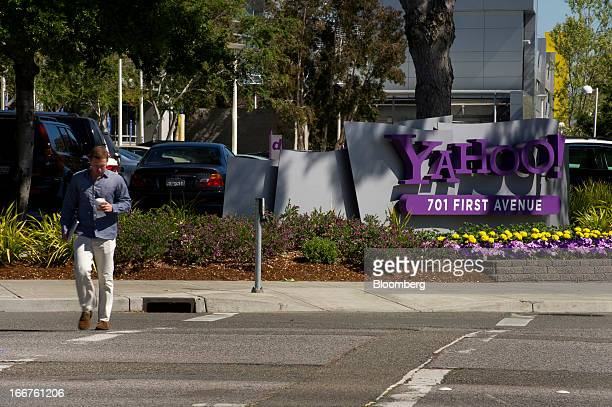 A pedestrian walks past Yahoo Inc signage displayed at the company's headquarters in Sunnyvale California US on Tuesday April 16 2013 Yahoo Inc the...