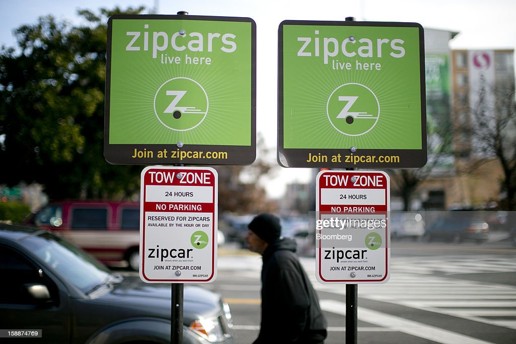 A pedestrian walks past Zipcar Inc. signs standing in the company's parking spaces in Washington, D.C., U.S., on Wednesday, Jan. 2, 2013. Avis Budget Group Inc., once a skeptic about car sharing services, agreed to buy short-term rental pioneer Zipcar for $491 million, signaling a shift in the industry to embracing drivers who don't want to own cars. Photographer: Andrew Harrer/Bloomberg via Getty Images