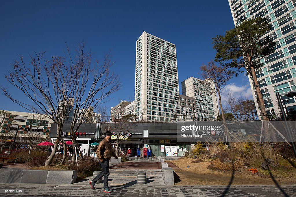 A pedestrian walks through a residential area in Sejong, South Korea, on Tuesday, Dec. 4, 2012. The construction of Sejong City 120 kilometers (75 miles) south of the capital fulfills the vision of the late President Roh Moo Hyun, who pledged to reduce the dominance of Seoul and pump money into a region courted for its swing voters. Photographer: SeongJoon Cho/Bloomberg via Getty Images