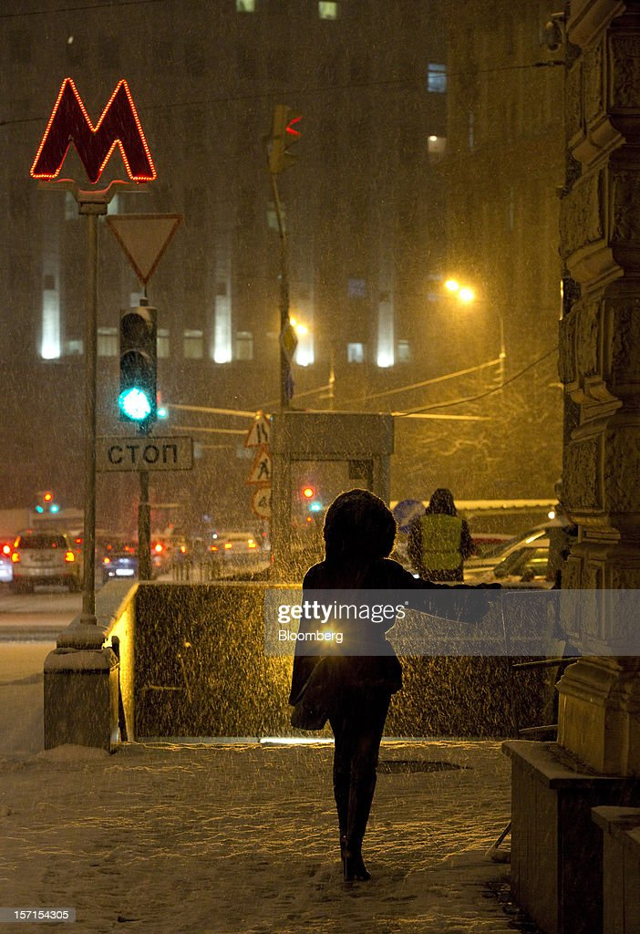 A pedestrian walks through snow outside Lubyanka metro station at night in Moscow, Russia, on Wednesday, Nov. 28, 2012. Bank Rossii proposes government create rule limiting increases of budget funds held at central bank, RIA Novosti reports, citing First Deputy Chairman Alexey Ulyukayev. Photographer: Andrey Rudakov/Bloomberg via Getty Images