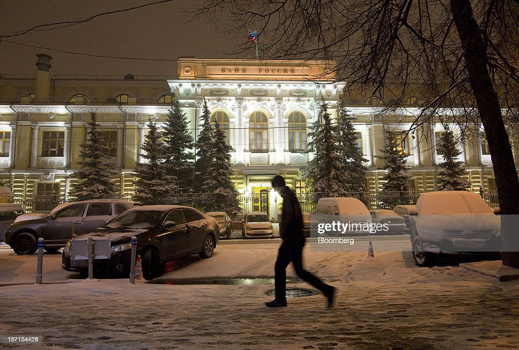 A pedestrian walks through snow past the front of Russia's central bank, Bank Rossii, in Moscow, Russia, on Wednesday, Nov. 28, 2012. Bank Rossii proposes government create rule limiting increases of budget funds held at central bank, RIA Novosti reports, citing First Deputy Chairman Alexey Ulyukayev. Photographer: Andrey Rudakov/Bloomberg via Getty Images