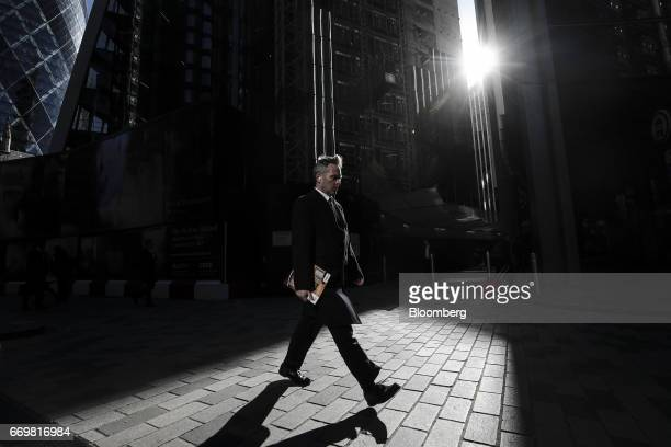 A pedestrian walks through the square mile financial district in London UK on Tuesday April 18 2017 Global banks have started arranging for some...