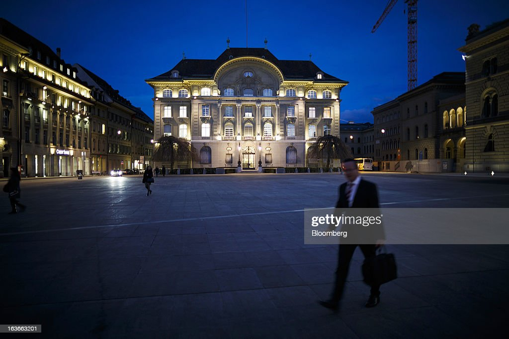 A pedestrian walks through the square outside the headquarters of the Swiss National Bank (SNB), center, Switzerland's central bank, in Bern, Switzerland, on Tuesday, March 12, 2013. The Swiss central bank pledged to keep up its defense of the franc cap after almost doubling its currency holdings to shield the country from the fallout caused by the euro zone's crisis. Photographer: Valentin Flauraud/Bloomberg via Getty Images
