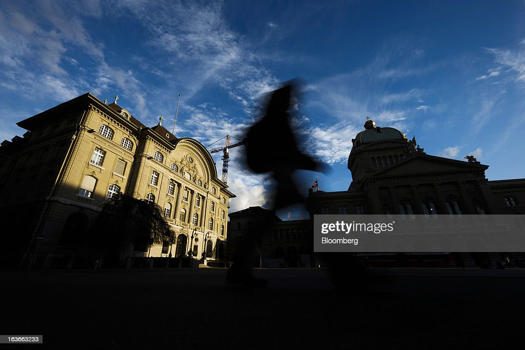 A pedestrian walks through the square outside the headquarters of the Swiss National Bank (SNB), left, Switzerland's central bank, in Bern, Switzerland, on Tuesday, March 12, 2013. The Swiss central bank pledged to keep up its defense of the franc cap after almost doubling its currency holdings to shield the country from the fallout caused by the euro zone's crisis. Photographer: Valentin Flauraud/Bloomberg via Getty Images