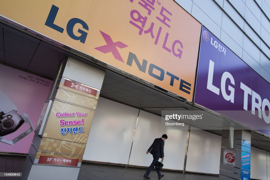 A pedestrian walks under advertisements for LG Electronics Inc. products in Seoul, South Korea, on Tuesday, Oct. 23, 2012. LG is scheduled to release third-quarter earnings today. Photographer: SeongJoon Cho/Bloomberg via Getty Images