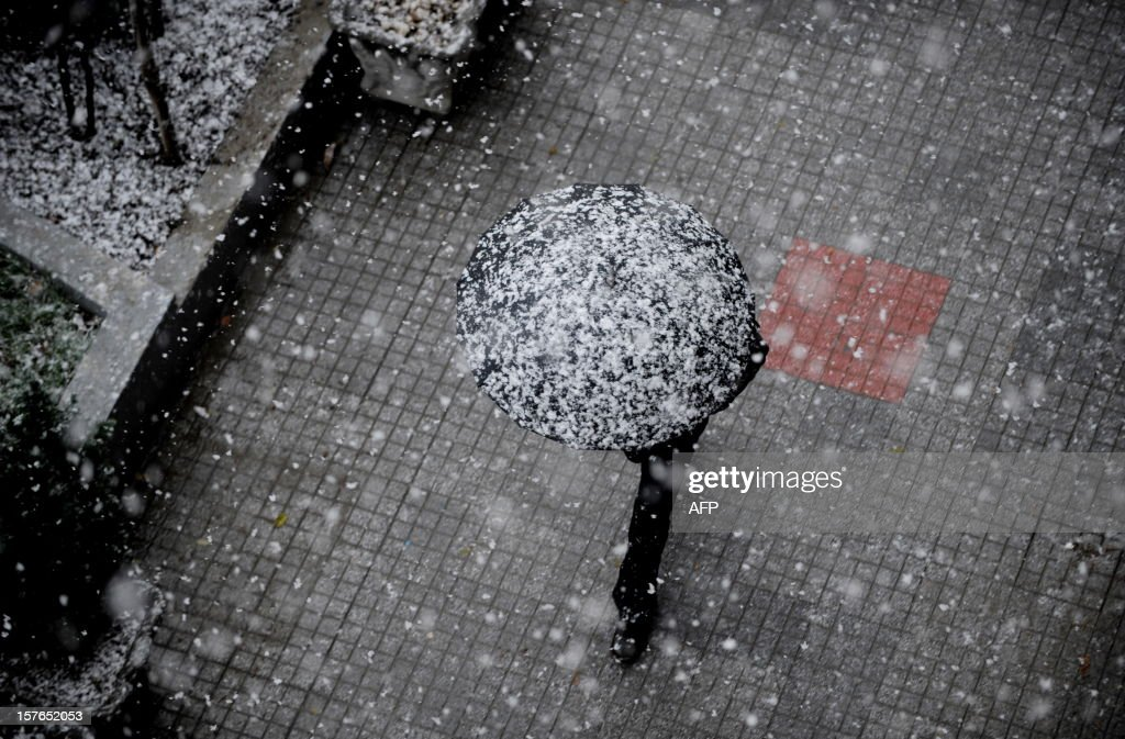 A pedestrian walks under his umbrella during a heavy snowfall in Pristina on December 5, 2012.