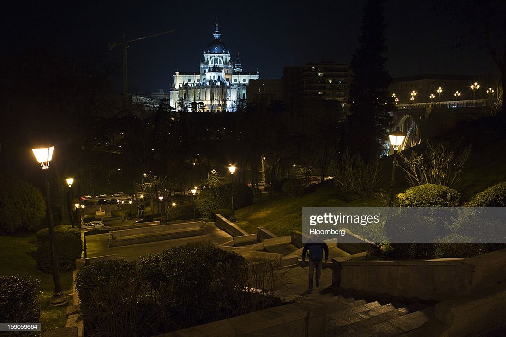 A pedestrian walks up a stairway illuminated by electric street lights near Santa Maria la Real de la Almudena cathedral in Madrid, Spain, on Sunday, Jan. 6, 2013. In December, the Spanish parliament passed an energy law that imposed a 7 percent tax on electricity generation from Jan. 1 to plug the deficit. Photographer: Angel Navarrete/Bloomberg via Getty Images