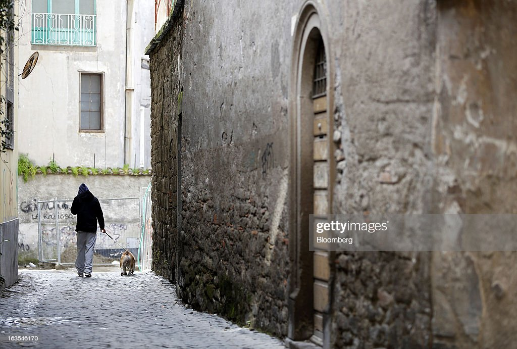 A pedestrian walks with a dog along a cobbled side street in Viterbo, Italy, on Monday, March 11, 2013. Intesa Sanpaolo SpA and UniCredit SpA are among Italian banks due to report losses for the fourth quarter this week, as the economic contraction meant more clients failed to repay their debts. Photographer: Alessia Pierdomenico/Bloomberg via Getty Images