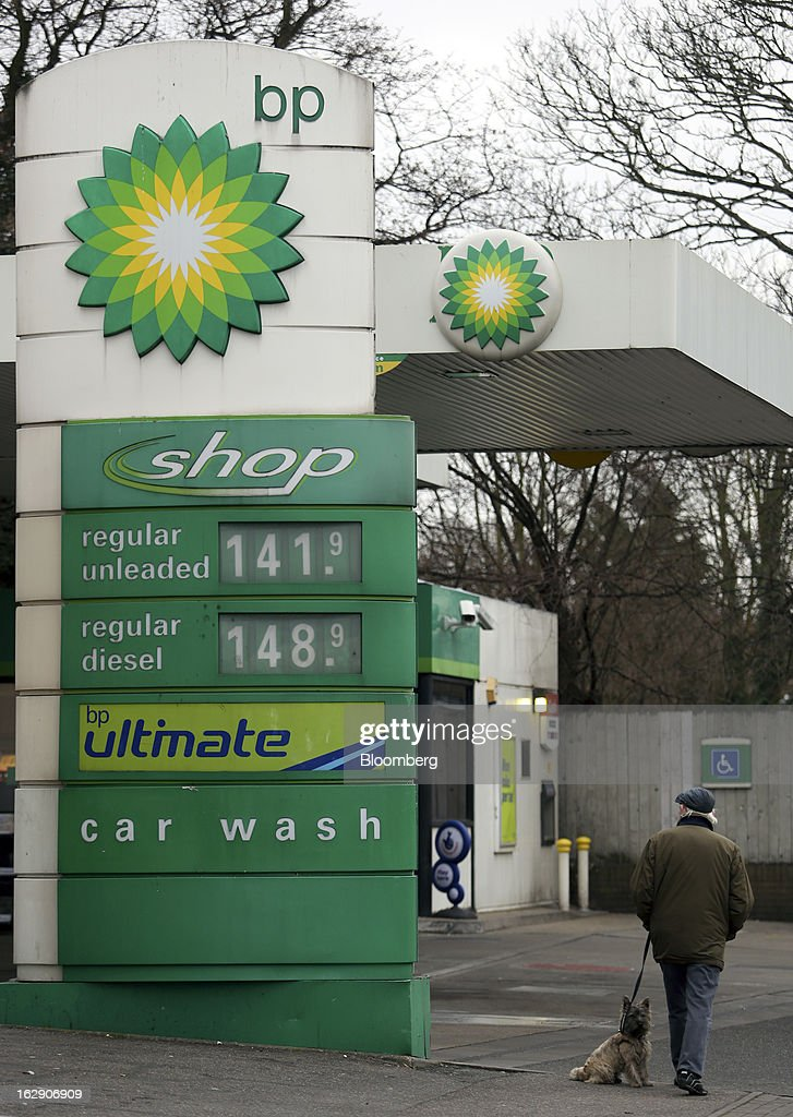 A pedestrian walks with a dog as they pass a BP gas station, operated by BP Plc, in Hornchurch, U.K., on Thursday, Feb. 28, 2013. BP Plc's push to maximize profits and cut costs at the Macondo well was a 'root cause' of the explosion that led to the 2010 Gulf of Mexico oil spill, a safety expert who studied the disaster said. Photographer: Chris Ratcliffe/Bloomberg via Getty Images