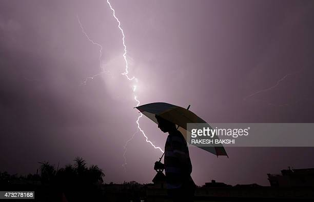A pedestrian walks with an umbrella as lightning strikes during an evening thunderstorm in Jammu on May 14 2015 AFP PHOTO / RAKESH BAKSHI / AFP /...