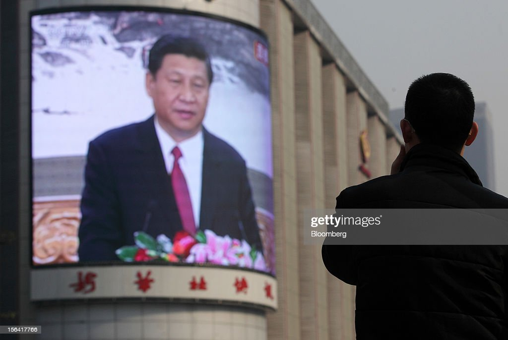 A pedestrian watches a monitor broadcasting a news conference by <a gi-track='captionPersonalityLinkClicked' href=/galleries/search?phrase=Xi+Jinping&family=editorial&specificpeople=2598986 ng-click='$event.stopPropagation()'>Xi Jinping</a>, general secretary of the Communist Party of China, outside a subway station in Beijing, China, on Thursday, Nov. 15, 2012. Xi replaced Hu Jintao as head of the Chinese Communist Party and the nation's military, ushering in the fifth generation of leaders who are set to run the world's second-biggest economy over the next decade. Photographer: Tomohiro Ohsumi/Bloomberg via Getty Images