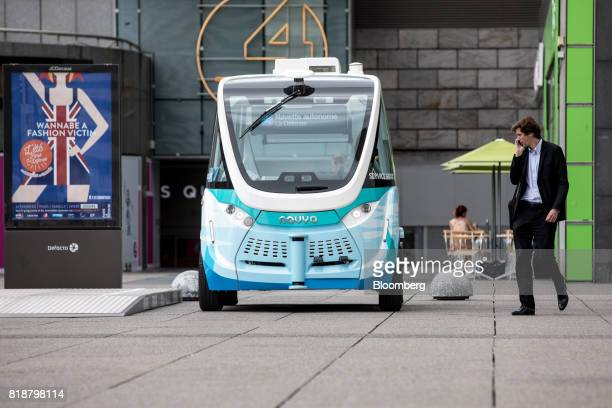 A pedestrian watches an Arma autonomous shuttle bus manufactured by Navya Technologies SAS as it travels in La Defense business district of Paris...