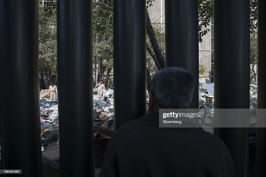 A pedestrian watches workers clean up debris at the Petroleos Mexicanos (Pemex) administrative building in Mexico City, Mexico, on Friday, Feb. 1, 2013. Pemex is stepping up security at oil production facilities as authorities investigate a blast that killed at least 33 people at the state-owned company's headquarters in Mexico City yesterday. Photographer: Susana Gonzalez/Bloomberg via Getty Images