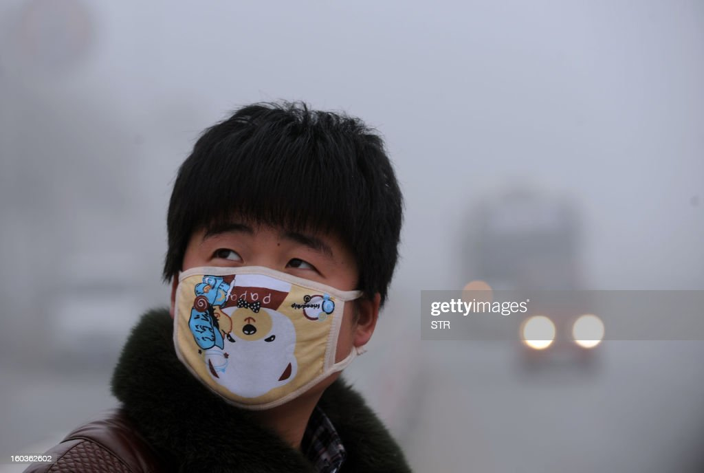 A pedestrian wearing a mask looks on in the heavy smog on a street of Haozhou, central China's Anhui province on January 30, 2013. Across China public frustration mounted this week as dense smog blanketed swathes of the country, with even state-run media questioning the authorities' ability to meet their goal of building a 'beautiful China'. CHINA OUT AFP PHOTO
