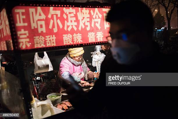 A pedestrian wearing a mask walks past a food stall on a polluted evening in Beijing on November 30 2015 Choking smog blanketed Beijing and much of...