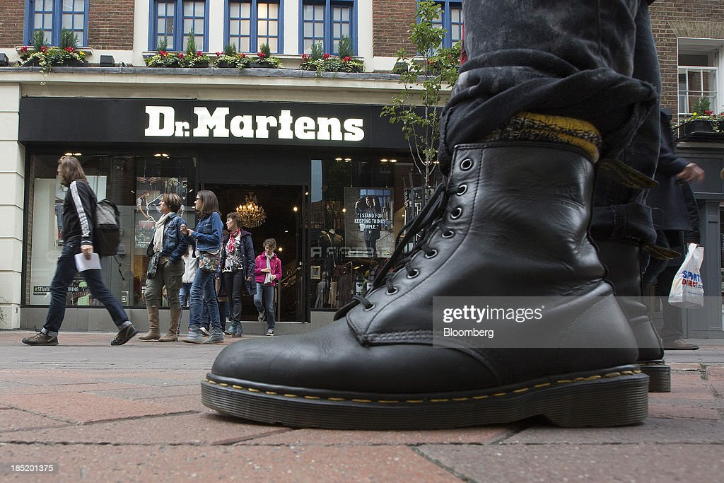 A pedestrian wearing Dr Martens boots poses for a photograph outside the footwear company's store in Convent Garden in London UK on Friday Oct 18...
