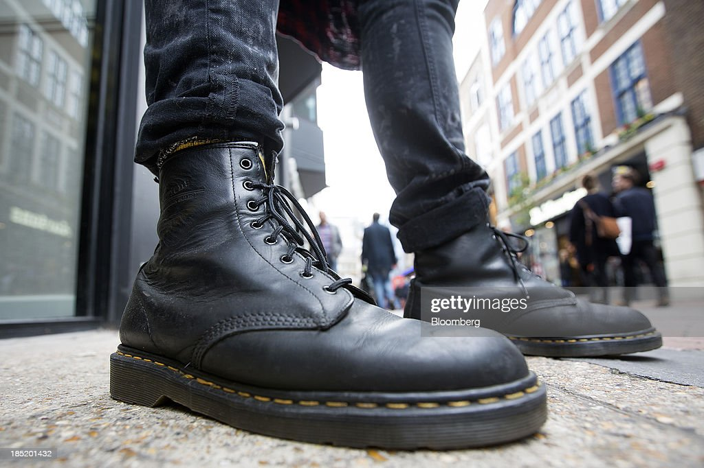 A pedestrian wearing Dr. Martens boots poses for a photograph outside the footwear company's store in Convent Garden in London, U.K., on Friday, Oct. 18, 2013. Permira Advisers LLP, the London-based private-equity firm that owns clothing brand Hugo Boss, is in advanced talks to buy iconic British punk-boot maker Dr. Martens, said a person with knowledge of the negotiations. Photographer: Simon Dawson/Bloomberg via Getty Images