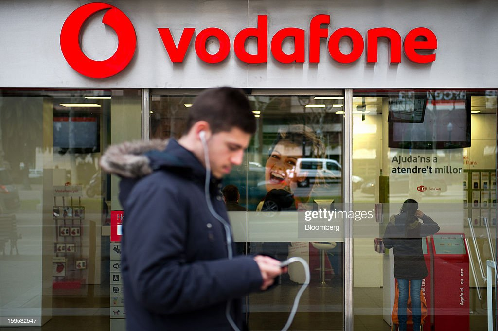 A pedestrian wearing headphones looks at his mobile phone as he passes the front of a Vodafone Group Plc store in Barcelona, Spain, on Tuesday, Jan. 15, 2013. Vodafone Group Plc, the world's second largest mobile-phone company, plans to reduce the workforce at its Spanish unit as unemployment exceeding 25 percent in the recession-plagued country causes sales to drop. Photographer: David Ramos/Bloomberg via Getty Images