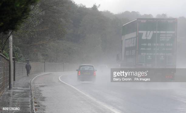 A pedestrian wearing weatherproof clothing walks on the Newry to Warrenpoint road Newry County Down as the bad weather continues