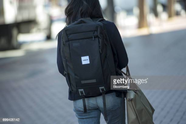 A pedestrian wears an Uber Technologies Inc backpack in front of the company's headquarters in San Francisco California US on Wednesday June 21 2017...